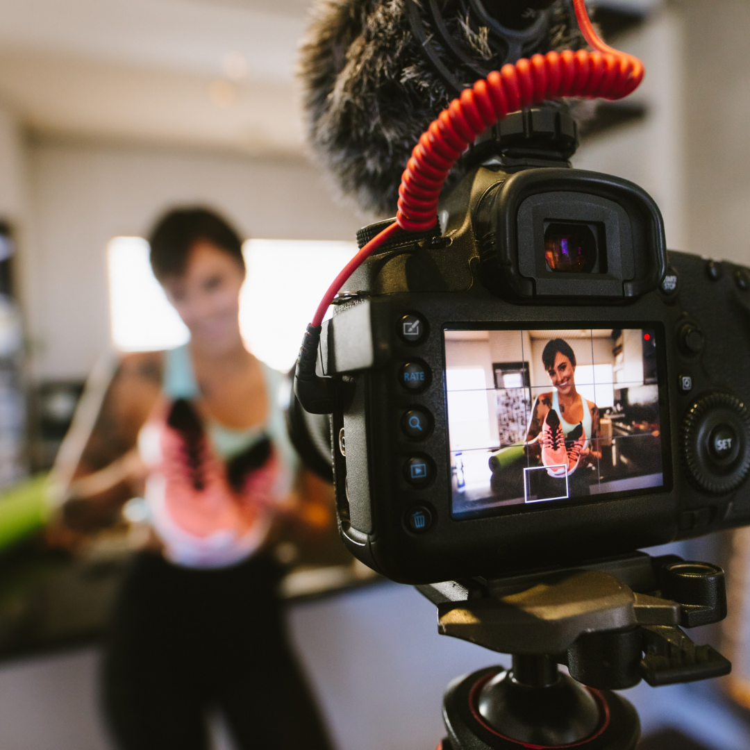 A female influencer is filming herself while holding up a pair of orange shoes and smiling at the camera.